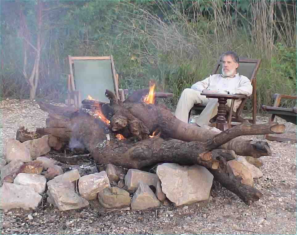JJ relaxes by the fire.  Firewood has to be shipped all the way to the camp, as it is forbidden to take any from the park.  Photo by FG, Dec. 2005.