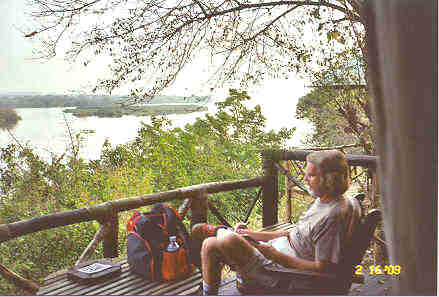 The 'Porch' in front of our tent offers a grand view across the Victoria Nile.  While we have a moment, I make entries in my journal.  Photo by Jungle Jim.
